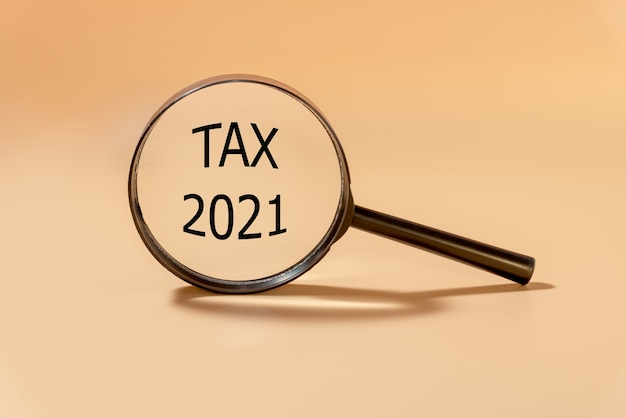 Magnifying glass with the word tax 2021. business and tax concept