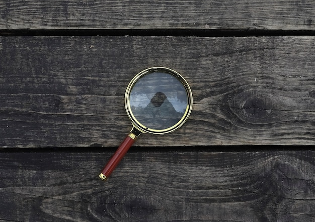 Magnifying glass on wood aged plank and timber background magnification