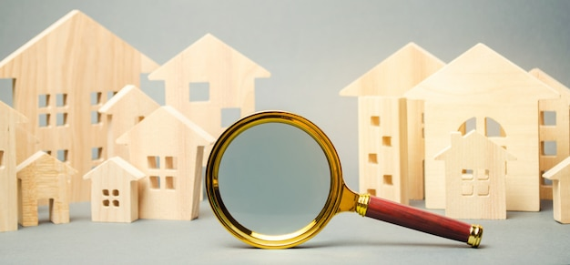Magnifying glass and wooden houses.