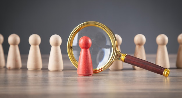 Magnifying glass and wooden human figures.  management. candidate selection