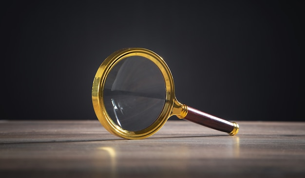 Magnifying glass on the wooden table.