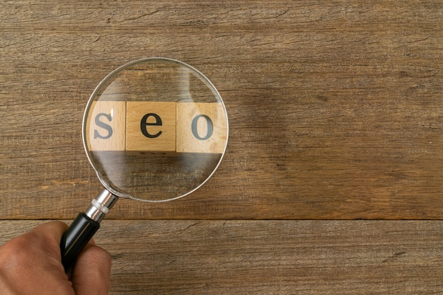 A magnifying glass and word seo on shabby wooden board.