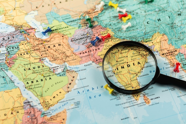 Magnifying glass on the world map selective focus at india. - economic and business concept.