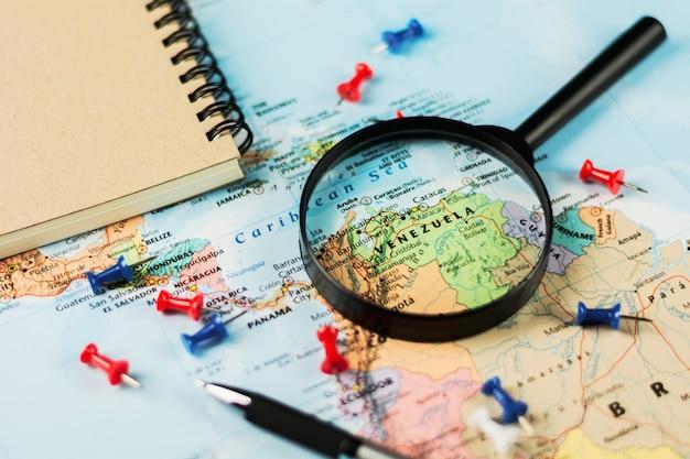 Magnifying glass on the world map selective focus at venezuela. - economic crisis concept.