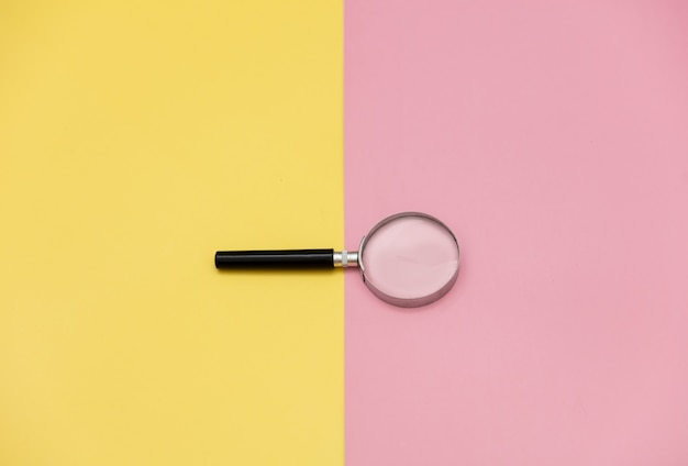 Magnifying glass on yellow and pink backgrounds.