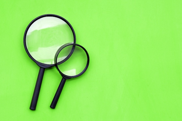 Magnifying glasses on green background. top view