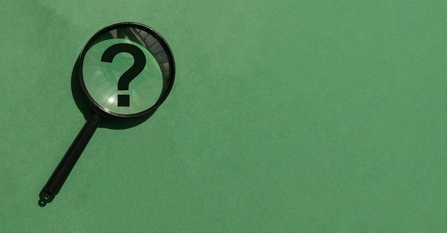 Magnifying lens over green background with copyspace banner with magnifier question mark and place f...