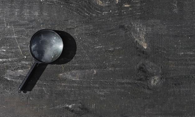Увеличительные линзы на деревянном старом фоне с копией пространства деревянный баннер с лупой