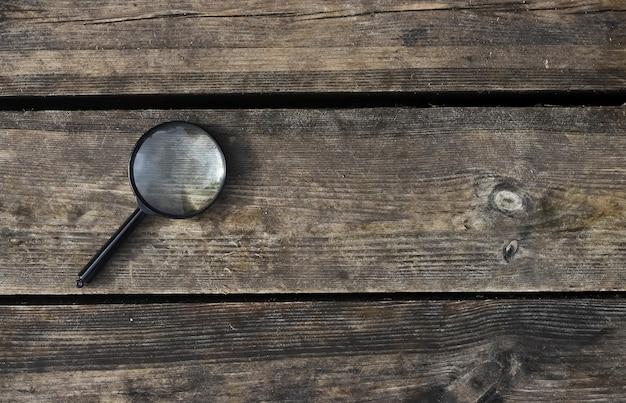 Увеличительная линза на деревянном естественном фоне с copyspace для текста