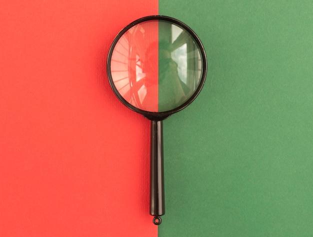 이중 톤 녹색 및 빨간색 배경 위에 렌즈를 확대합니다. 검색 및 연구 개념.