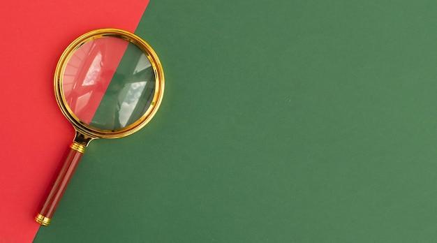 텍스트에 대 한 녹색과 빨간색 backgroundwith 복사 공간 위에 돋보기 렌즈. copyspace와 검색 도구입니다.
