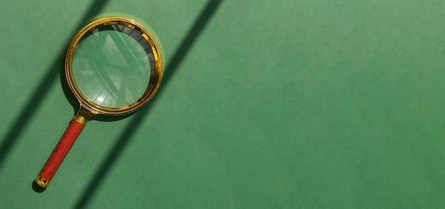 Увеличительная линза на зеленом фоне с copyspace для текстового баннера с золотой лупой и копией пространства