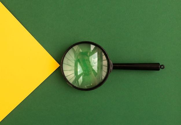 노란색 광선으로 녹색 배경 위에 렌즈를 확대합니다. 검색 도구. 답을 찾는 개념.