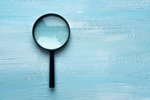 Magnifying magnifier lies on a painted wooden background