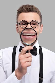 Увеличивающая улыбка. портрет веселого молодого человека в галстуке-бабочке и подтяжках, держащего увеличительное стекло перед ртом и улыбающегося