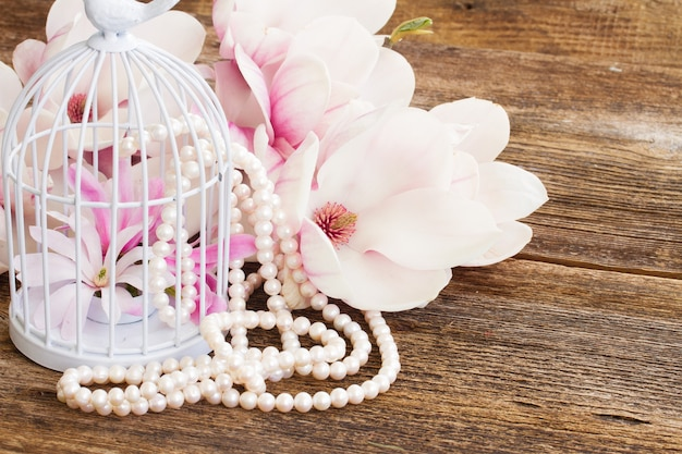 Magnolia flowers with pearls and birdcage on wooden table
