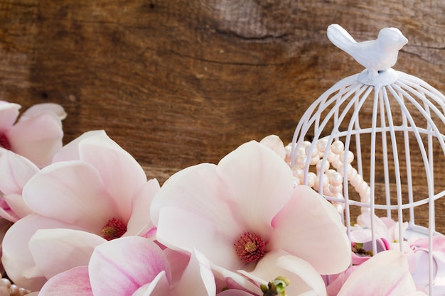 나무 테이블에 새 장과 목련 신선한 꽃