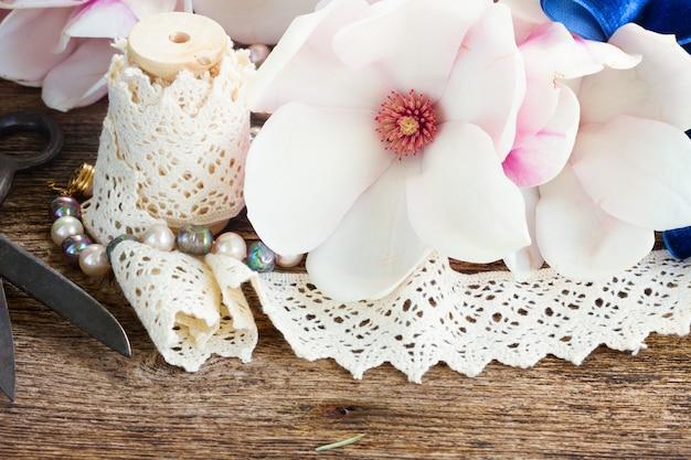 진주와 나무 테이블에 빈티지 레이스와 목련 신선한 꽃