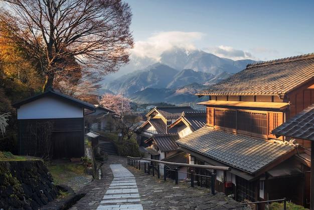 岐阜県中津川市木曽谷、日の出に中央アルプス山がある中山道の丘の上にある馬籠柔術保存町。建物のファサードと春の桜の有名な旅行のランドマーク。