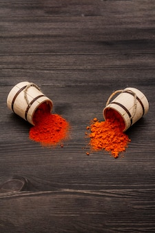 Magyar brilliant red sweet and hot paprika powder. traditional seasoning for cooking national food. wooden kegs, black wooden