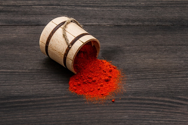 Magyar brilliant red sweet paprika powder. traditional seasoning for cooking national food. wooden keg, black wooden
