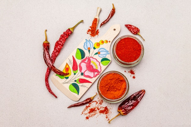Magyar (hungarian) red sweet and hot paprika powder. traditional pattern on a cutting board, different varieties of dry pepper.