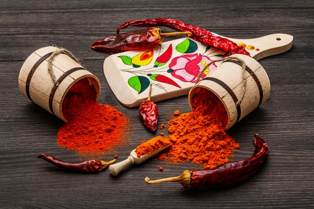 Magyar red sweet and hot paprika powder. traditional pattern on a cutting board, different varieties of dry pepper. black wooden