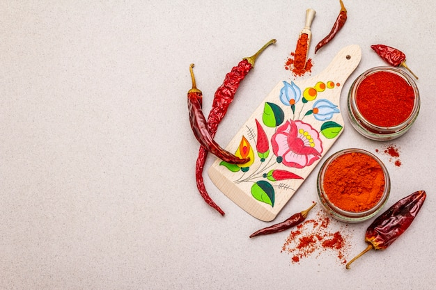 Magyar red sweet and hot paprika powder. traditional pattern on a cutting board, different varieties of dry pepper. stone concrete