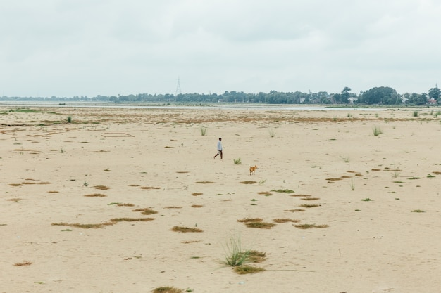 Человек и собака гуляя на малую воду около виска mahabodhi на bodh gaya, бихара, индии.