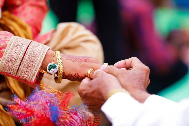 ヒンドゥー教のマハラシュトラの結婚式で、金の指輪を指に入れる新郎