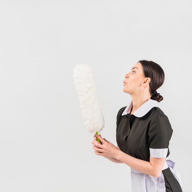 Maid blowing on duster