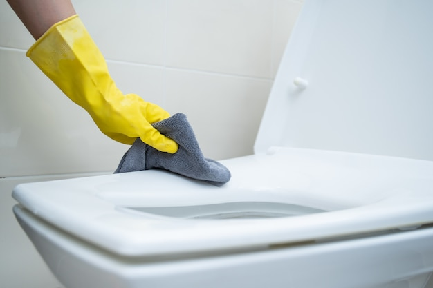 Maid cleaning flush toilet by using alcohol and liquid cleaning solution.  sanitation and healthcare.