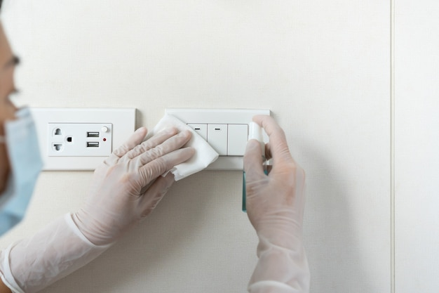Maid cleaning a light switch with wet wipe, alcohol spray. disinfection surface concept
