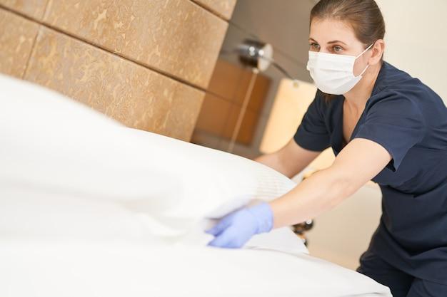 Горничная в маске взбивает белую подушку на кровати, убирая номер в отеле. концепция гостиничного обслуживания