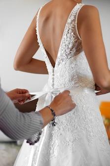 メイド・オブ・オナーは、花嫁が彼女の手にクローズアップで後ろで弓を結ぶ彼女のエレガントな白いウェディングドレスを着るのを手伝っています