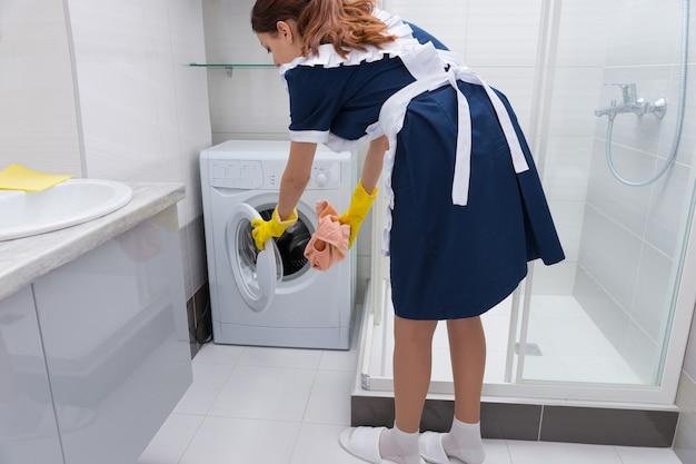 白いタイル張りのバスルームのシャワー室の隣にある小さな洗濯機にピンクのタオルを置くメイド