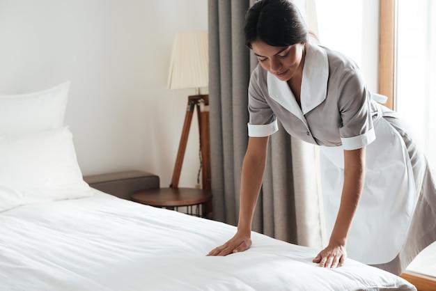 ホテルの部屋で白いベッドシートを設定するメイド