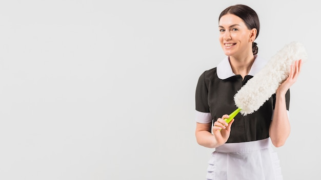 Maid in uniform smiling with duster