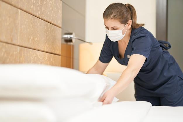 Горничная в маске убирает спальню после гостей в гостиничном номере. концепция гостиничного обслуживания