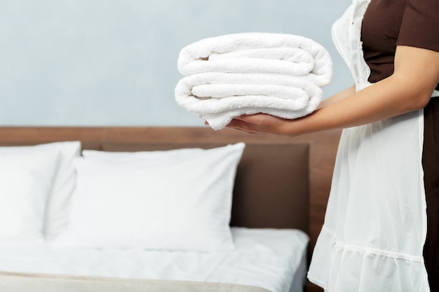 Maid with fresh clean towels during housekeeping in a hotel room