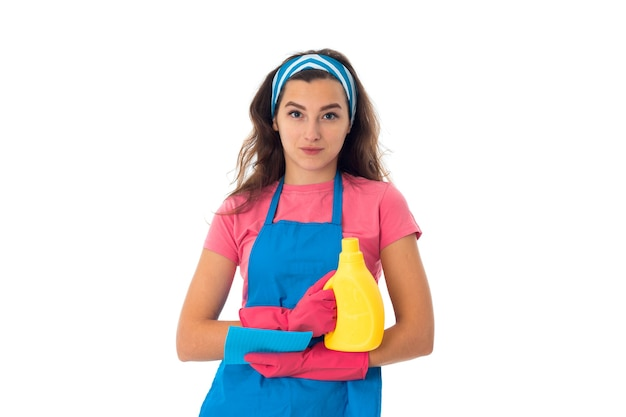 Maid woman in an apron with cleansers isolated on white wall