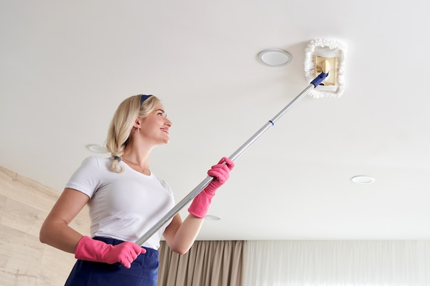 Maid woman holding mop pile, cleaning ceiling in living room. house cleaning service concept.
