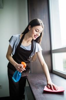 Горничная молодая женщина с инструментами. концепция услуги по уборке дома.