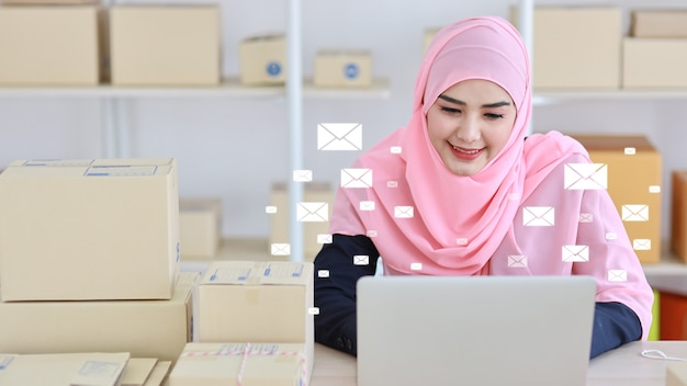 Mail communication technology concept. young smart asian muslim businesswoman working on computer, mobile smartphone receiving and sending customers e-mail with notification message icons above device
