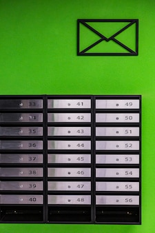 Mailboxes in an apartment building, made of stainless steel, on a green wall
