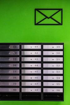緑の壁にある、ステンレス鋼製のアパートのメールボックス