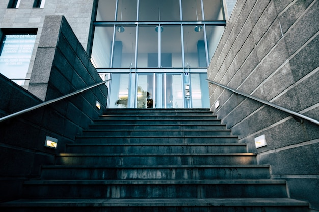 Main entrance door for commercial district like bank or insurance with people working inside - urban concept and modern town place - stairs and glass doors