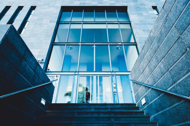 Главная входная дверь в коммерческий район, например, банк или страховка с людьми, работающими внутри - урбанистическая концепция и современная городская местность - лестницы и стеклянные двери