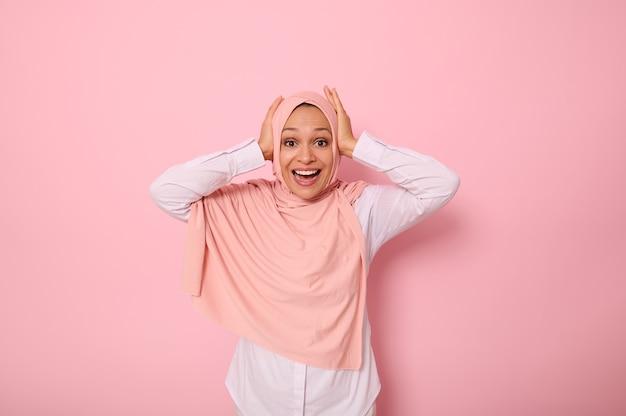 분홍색 히잡을 쓴 이슬람 여성의 얼굴 표정에 중점을 두고 손으로 머리를 잡고 놀란 표정으로 카메라를 쳐다보며 이빨 미소를 띠고 웃고, 복사공간을 복사합니다.