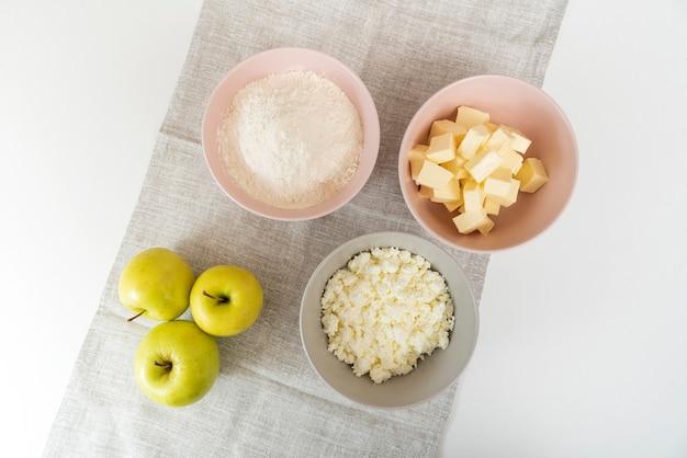アップルパイの主な材料。小麦粉、バター、カッテージチーズ、リンゴのプレート。上面図。